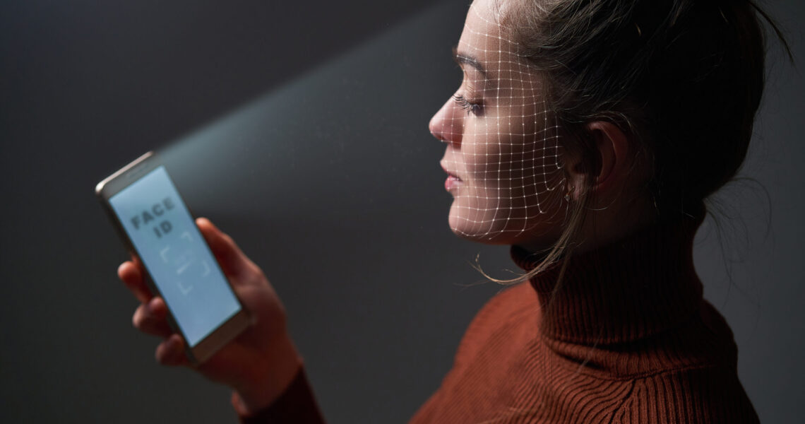 Female scans face using facial recognition system on mobile phone for biometric identification. Future hi tech technology and face id