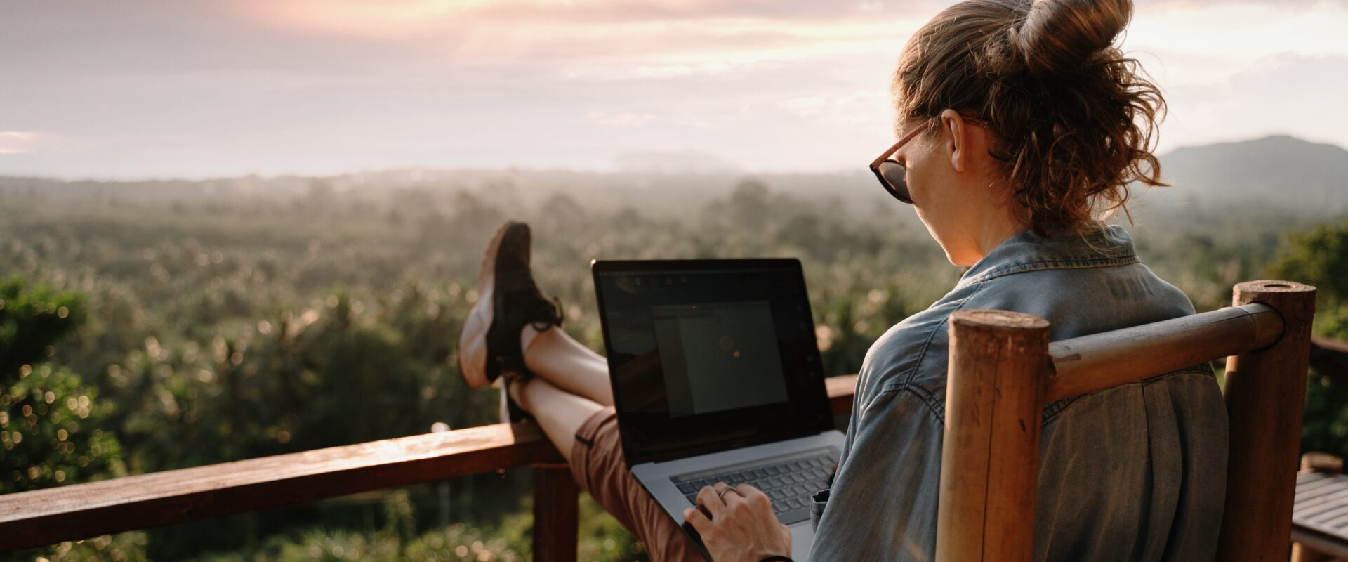 Young business woman working at the computer in cafe on the rock. Young girl downshifter working at a laptop at sunset or sunrise on the top of the mountain to the sea, working day.