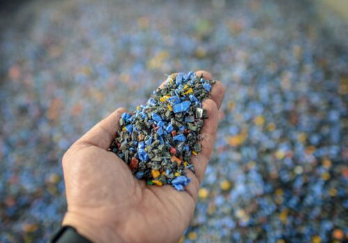 Hand holding recycled plastic chips as raw material in production.